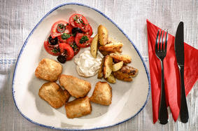 Kibbles with potato wedges and aoili on tomato salad